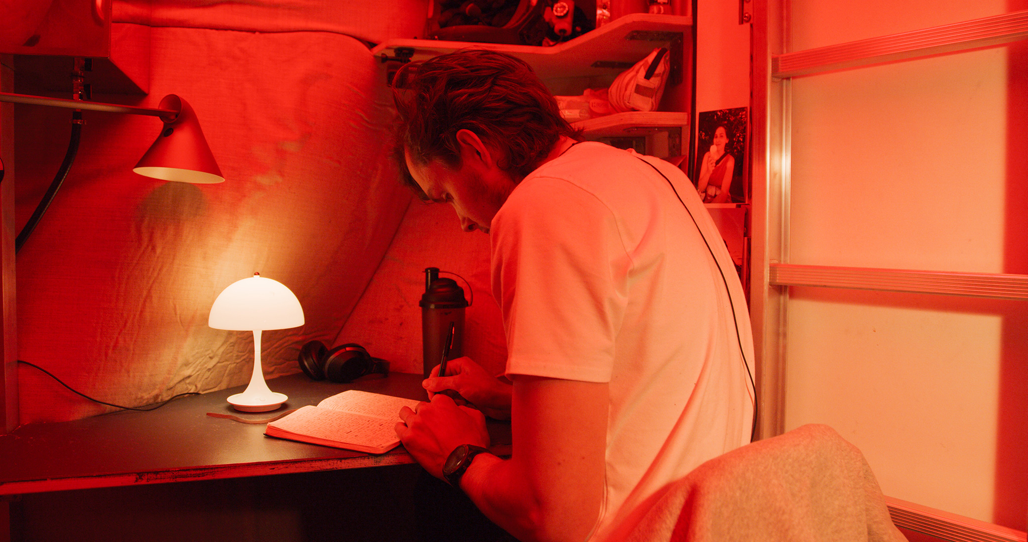 Karl-Johan sitting at his desk inside the Habitat writing in his notebook